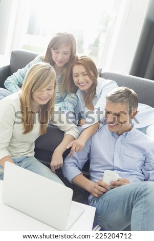 Happy parents with daughters using laptop in living room #225204712