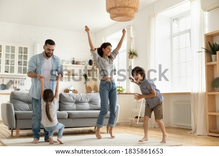 Happy parents with kids dancing in modern living room, having fun, playing active game, overjoyed mother and father with children siblings dancing to favorite music, jumping, celebrating event