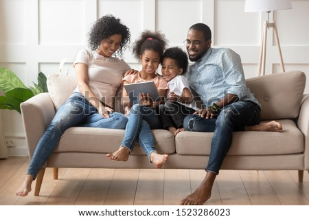 Happy parents with smiling kids sitting on sofa, using tablet looking at screen, watching cartoons online, funny videos together, little girl showing family photos on gadget, making order, ecommerce stock photo