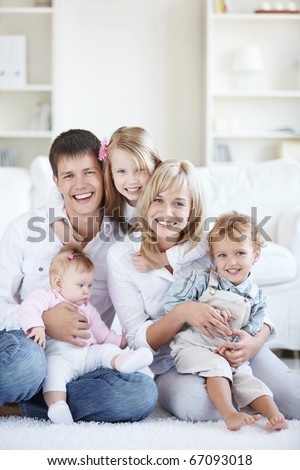 Happy parents with three children at home