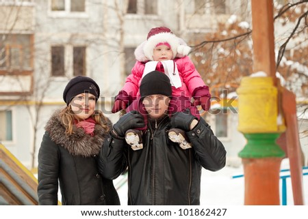 Happy parents with toddler  in winter street