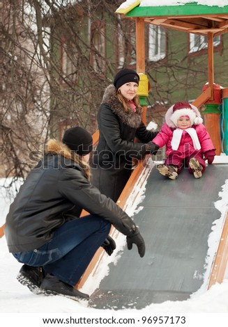 happy parents with  toddler playing on slide in winter