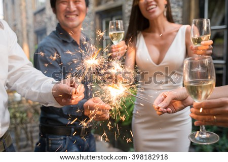 Happy party guests with Bengal lights and champagne glasses #398182918