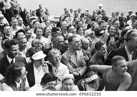 Happy passengers standing on crowded ship deck