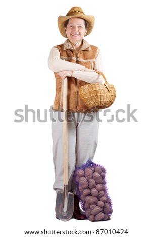 Happy pastoral  woman  with spade and harvested potato over white - stock photo