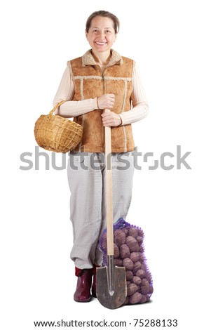 Happy pastoral  woman  with spade and harvested potatoes over white