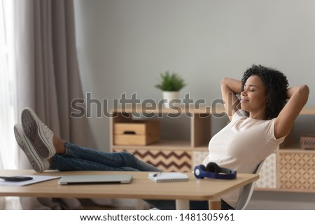 Happy peaceful african American young woman in casual clothes relax in chair hands over head legs on desk, peaceful black millennial girl rest with eyes closed sit at workplace, stress free concept