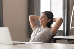 Happy peaceful asian female employee lean on comfortable office chair, holding hands behind head, relaxing during working day break or after completed job, looking aside, dreaming about vacation.