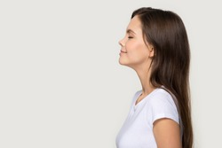 Happy peaceful millennial girl stand in profile side view isolated on grey studio background, calm young woman in white t-shirt with eyes closed face blank copy space, massage or healthcare sale offer