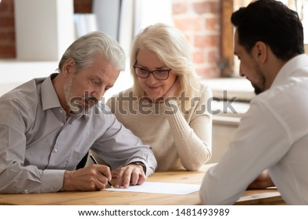 Happy pensioner couple sign contract with male realtor or broker buying house or property together, excited mature husband and wife put signature on document close deal with bank specialist