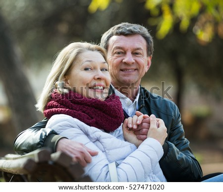 Happy pensioners cuddling in park and enjoying time together #527471020