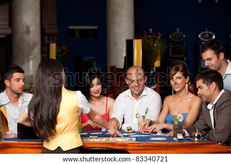 happy people and dealer playing blackjack