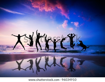 Happy people and dog jumping together on the sunset beach #96034910