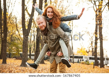 Happy people are jumping, having fun. Two young lovers and beautiful people for a walk in the park. The love story of two lovers. Reddish haired woman and a man with a beard. Autumn love Story two.