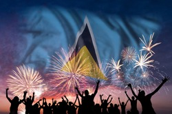 Happy people are looking holiday fireworks with flag of Saint Lucia in sky, independence day