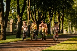 Happy people biking outdoors. Group of friends enjoying summer vacation. Students are travelling by bikes.