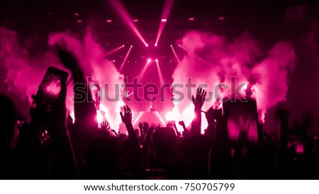 Happy people dance in nightclub party concert and listen to the music from DJ on the stage in the background.