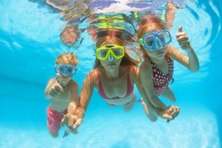 Happy people dive underwater with fun. Funny photo of mother, kids in snorkeling masks in aqua park swimming pool. Family lifestyle, children water sport activity, lesson with parent on summer holiday