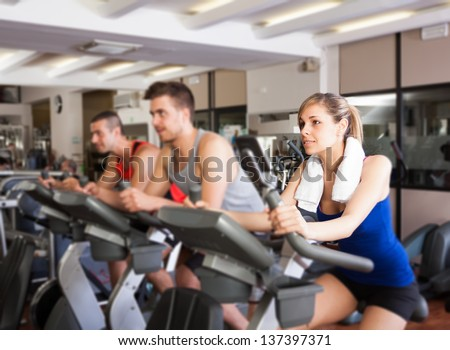 Happy people doing indoor biking in a fitness club
