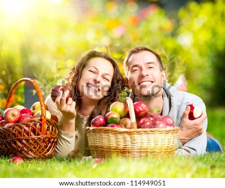 Happy People Eating Organic Apples in Autumn Garden.Healthy Food.Outdoors.Park Basket of Apples.Harvest concept Smiling Couple Relaxing on Grass