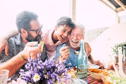 Happy people family concept laugh and have fun together with three different generations ages : grandfather father and young teenager son all together eating at lunch - outdoor home party leisure