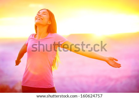 Happy people - free woman enjoying nature sunset. Freedom and serenity concept with female model in ecstatic enjoyment. Mixed race Asian Caucasian female model in 20 enjoying sunset, Grand Canyon, USA
