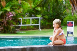 Happy people have fun at pool side edge. Funny photo of little child relaxing in outdoor swimming pool. Family lifestyle, kids water sport activity with parents on summer holiday
