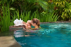 Happy people have fun at pool side edge. Funny photo of young mother with child relaxing in outdoor swimming pool. Family lifestyle, kids water sport activity with parents on summer holiday