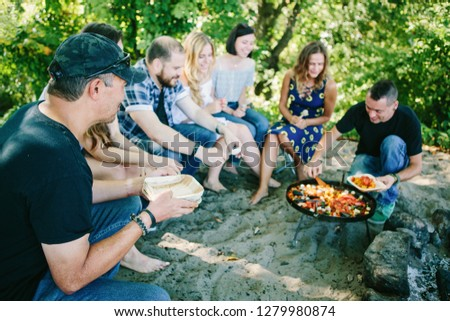 Happy people having a pic-nic. Group of friends making barbecue in the nature. Concept about good and positive