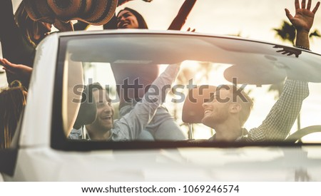 Happy people having fun in convertible car at sunset - Young friends dancing and making party on cabriolet auto outdoor - Focus on right man face - Travel, youth lifestyle and friendship concept