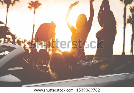 Happy people having fun in convertible car at sunset - Young friends making party on cabriolet auto outdoor - Focus on left blond girl head - Travel, youth, lifestyle and friendship concept