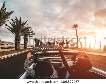 Happy people having fun in convertible car in summer vacation at sunset - Young couple enjoyng  holiday on cabrio auto outdoor - Travel, youth lifestyle and wanderlust concept - Focus on hands #1308879487