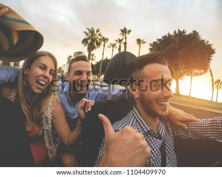 Happy people having fun in convertible car in summer vacation - Miillennials friends laughing on cabriolet auto - Travel, youth lifestyle, holidays and wanderlust concept - Main focus on left couple