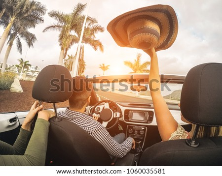 Happy people having fun in convertible car in summer vacation - Young friends laughing on cabrio auto outdoor - Main focus on man head - Travel, youth lifestyle, holidays and friendship concept - Shutterstock ID 1060035581