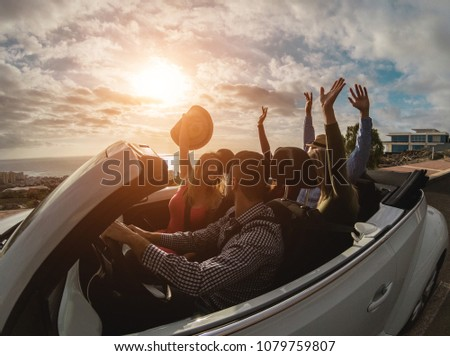 Happy people having fun together in convertible car in summer vacation - Young tourist friends traveling in cabriolet auto - Travel, youth lifestyle and holiday concept - Main focus on hands