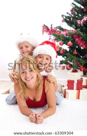 Happy people in front of christmas tree playing together - partially isolated
