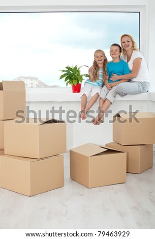 Happy people in their new home among cardboard boxes - sitting on the windowsill with a potted plant