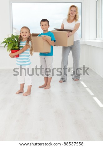 Happy people in their new home with boxes and potted plant
