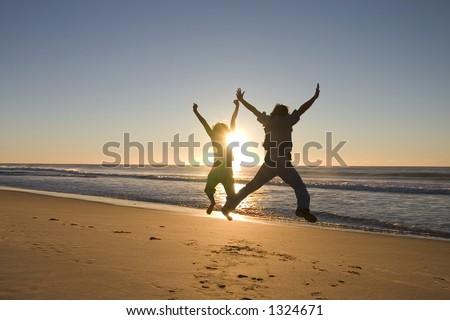 Happy people jumping around at sunrise