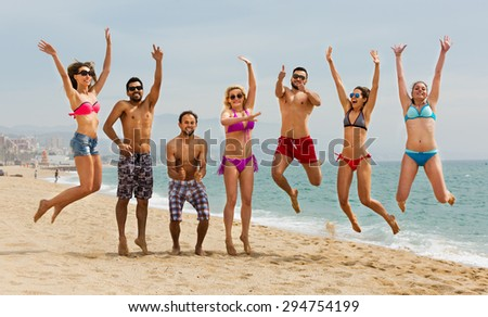 Happy people jumping at beach