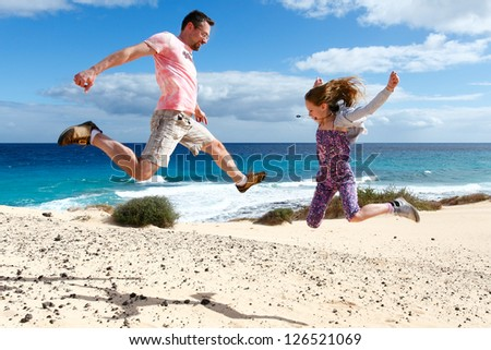 Happy people jumping on a beach. A girl and her father enjoying their vacations