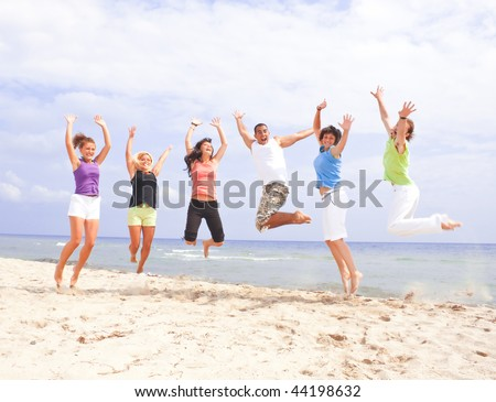 Happy people jumping on the beach by the sea