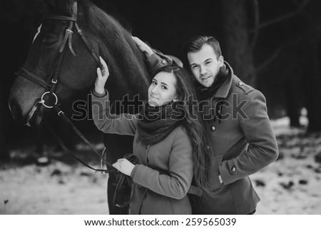 Happy people outdoors with horse and couple in love. Black and white photo
