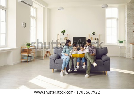Happy people sitting together on sofa in modern interior of new house or studio apartment. Family with kids reading book on comfy gray couch in the living-room and enjoying quiet leisure time at home