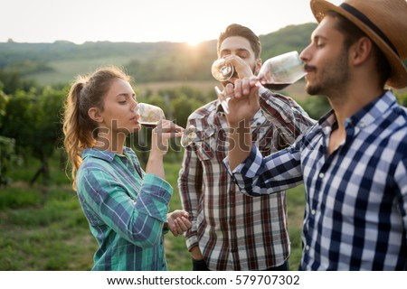 Happy people tasting wine in vineyard #579707302
