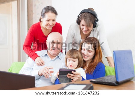 Happy people  uses few various electronic devices in home