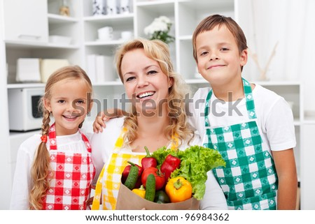 Happy people with healthy food in the kitchen