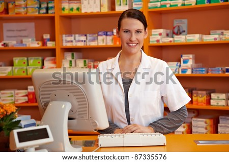 Happy pharmacist standing at checkout counter in a drugstore