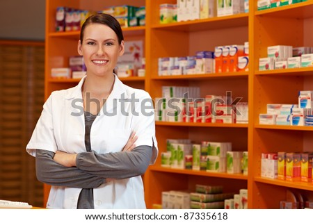 Happy pharmacist with her arms crossed in a drugstore