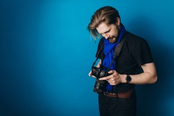Happy photographer in stylish clothes reviewing taken photos on digital camera. Isolated over blue studio background. Concept of photography.